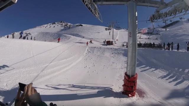 Menino fica pendurado em cadeira de teleférico sobre pista de esqui