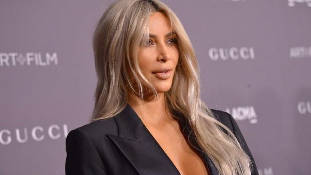 Kim Kardashian vai a evento com blazer aberto e sem sutiã
