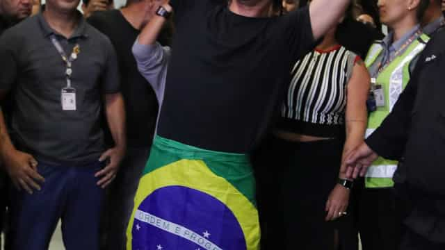 Medina desembarca com festa e bandeira do Brasil enrolada no corpo