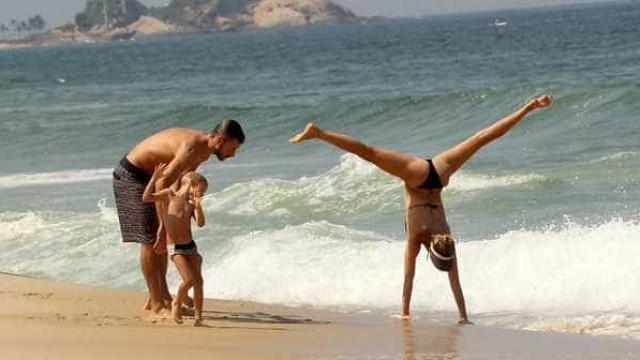 Fernanda Lima faz acrobacia em praia com família