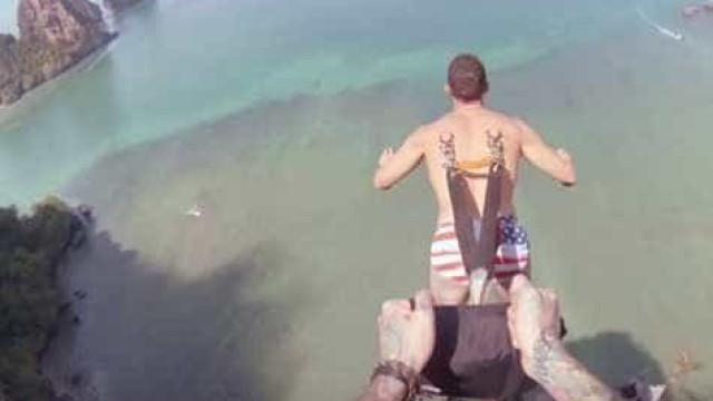 Homem salta com ganchos de paraquedas cravados na pele