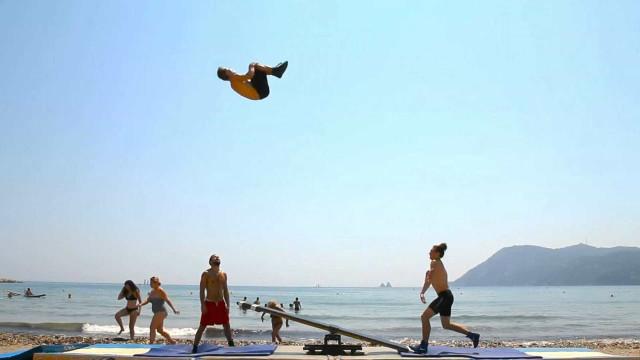 Ginastas se divertem fazendo acrobacias com gangorra  na praia