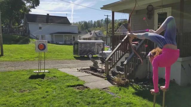 Menina estoura balão com arco e flecha de ponta-cabeça