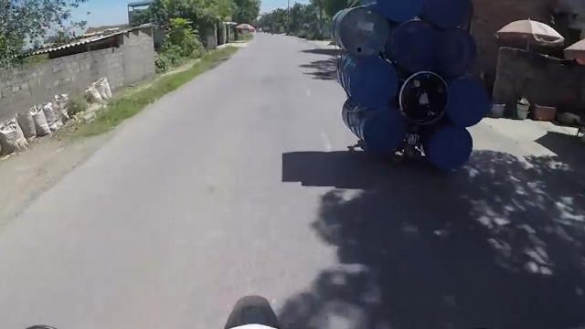 Homem carrega dez barris em motocicleta no Vietnã; assista