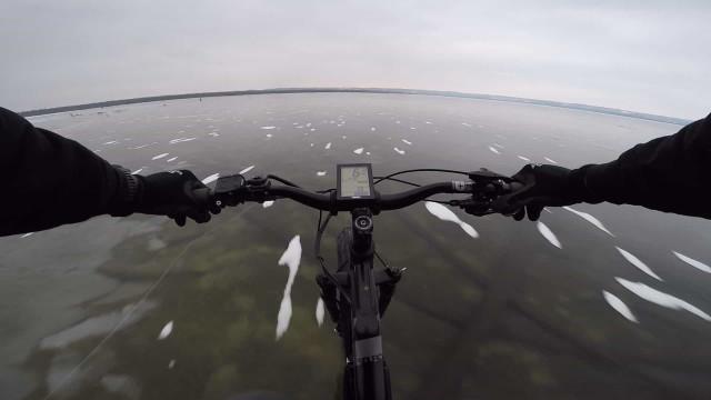 Ciclista atravessa lago congelado transparente