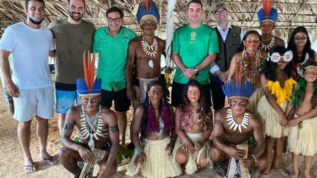 Flávio e Eduardo Bolsonaro posam sem máscaras ao lado de indígenas no Amazonas