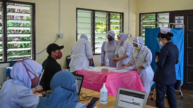 """Enfermeira exausta dá """"vacina vazia"""" a mulher na Malásia"""