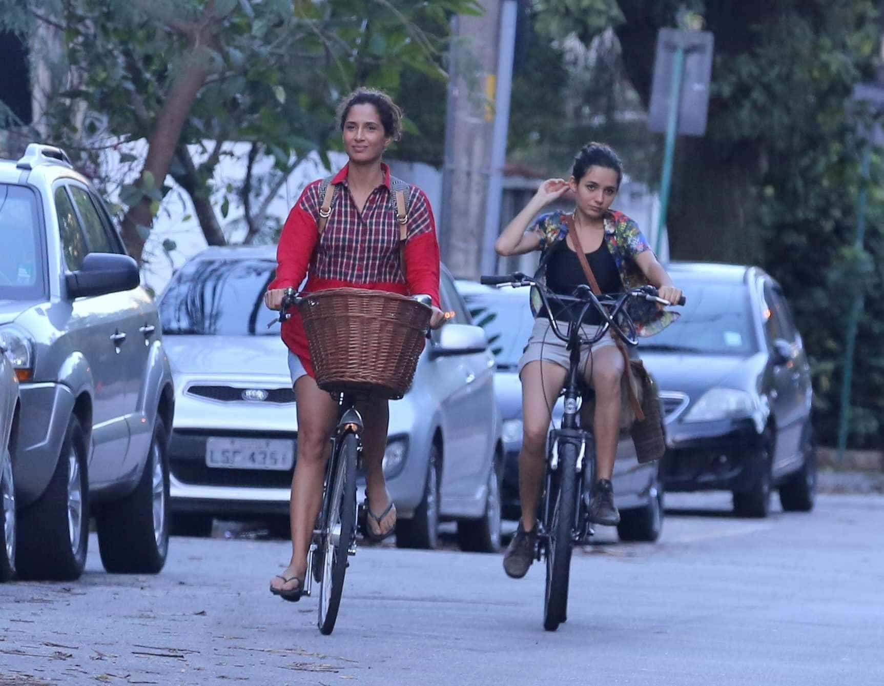 Em rara aparição, filha de Camila Pitanga pedala ao lado da mãe